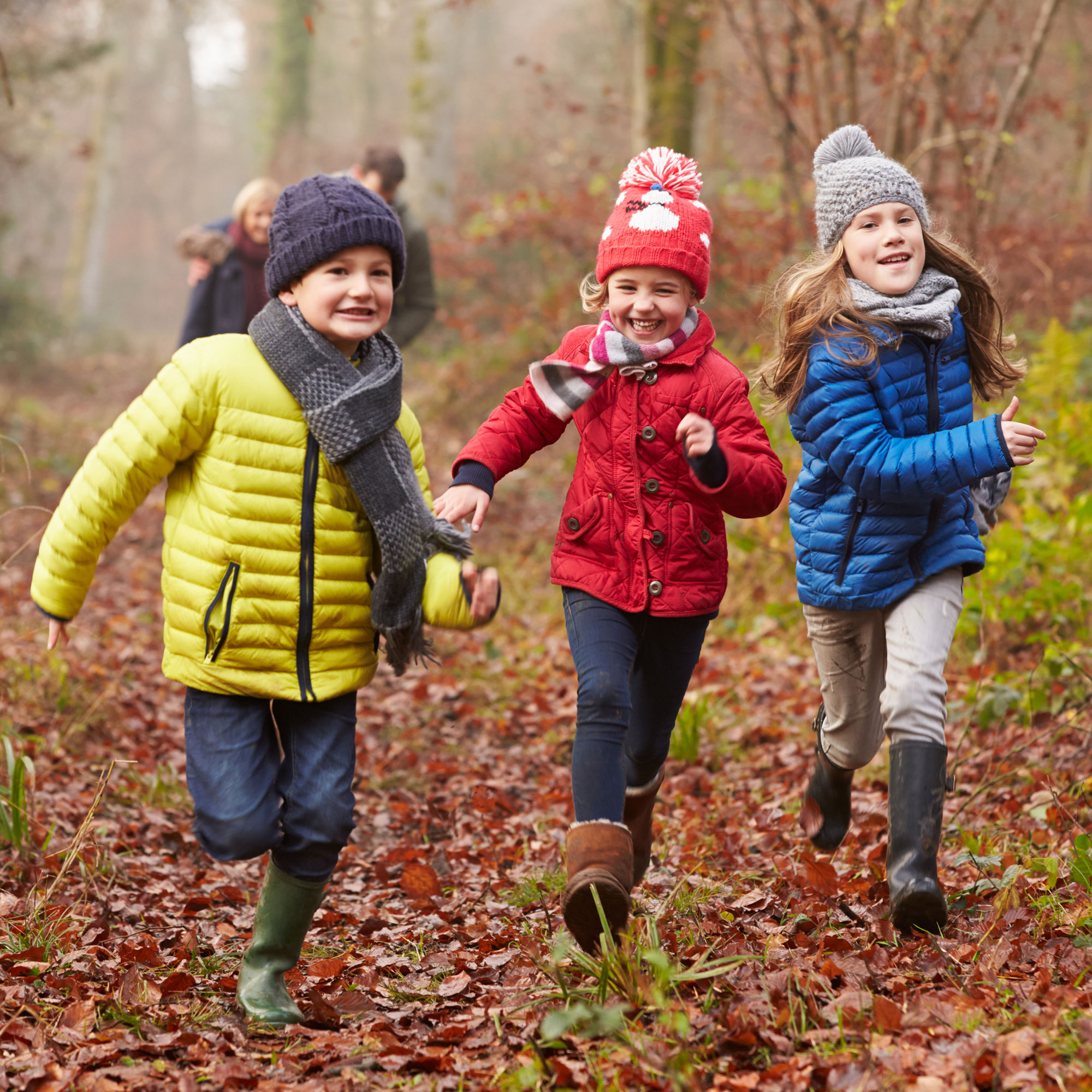 Three happy kids running in the forest.